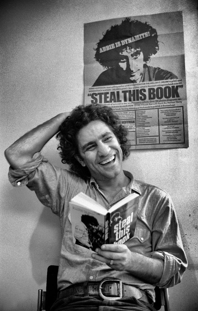 Photograph of Abbie Hoffman holding a copy of